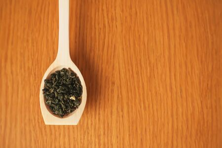 A wooden background on which lies a handmade wooden spoon filled with leaves of fragrant green tea. Zdjęcie Seryjne