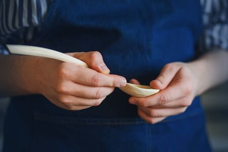 A woodworker in a blue apron is holding an elegant handmade wooden spoon.