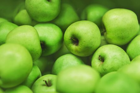 Green ripe sweet delicious apples are lying in a pile in the grocery store. Vegetarianism. Fruit.