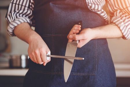 A chef in a striped shirt and blue apron stands in the kitchen sharpening the blade of a steel knife in the sunlight.