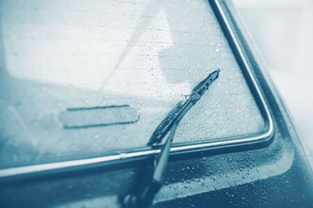 The black windshield wiper on the back window of the car, which is wet from raindrops on a quiet, cloudy, foggy day. Melancholy. Bad weather.
