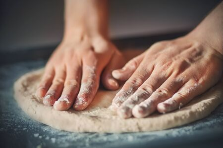 A man with his hands rolls out homemade pizza dough, lying on a dark baking tray and illuminated by light. Cooking at home.