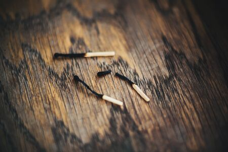 Three burnt-out thin matches lie on an old wooden table. One of them broke. Death.