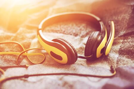 Large yellow headphones with a microphone and a long wire lie on a soft plaid blanket on the bed, illuminated by bright sunlight. Фото со стока