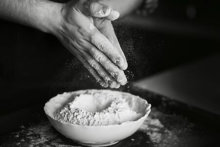 Black-and-white image of the process of cooking homemade dough. The cook mixes the flour with the other ingredients on the plate and shakes the flour off his hands. 版權商用圖片