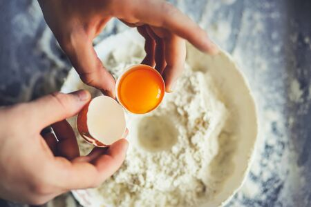 The cook is holding a broken chicken egg with the yolk in the shell and is going to mix it with flour in a white bowl. Home baking process. Фото со стока