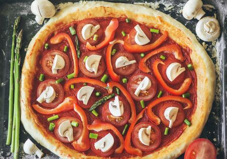 Delicious Italian vegetarian homemade pizza with asparagus, tomatoes and mushrooms is on a baking tray. Home cooking. Фото со стока