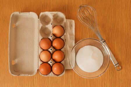 Top view of baking ingredients on a wooden table - chicken eggs in a cardboard box, granulated sugar in a glass bowl and a whisk for mixing them. Фото со стока