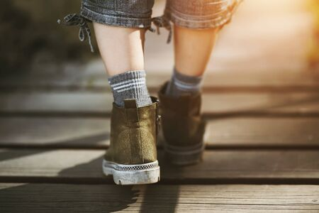 The slender legs of a woman in rough boots, grey jeans and socks, walking carelessly along a wooden path in the sunlight.