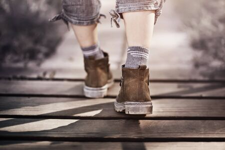 Elegant feet of a girl in rough boots in gray jeans and socks walk along a path made of wooden planks on a bright day. Фото со стока