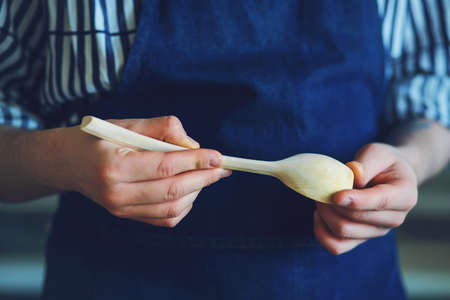 A man in a blue apron and striped shirt is holding a beautiful hand-carved wooden spoon. Фото со стока
