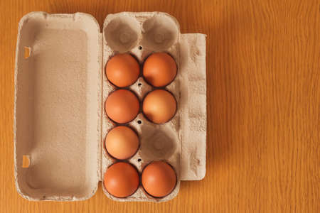A cardboard box from the store with brown chicken eggs stands on a wooden table. The view from the top.