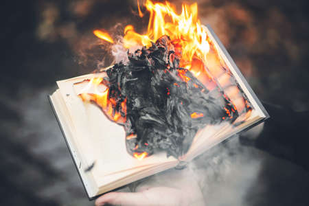 A person holds an old book in his hands, the pages of which with wise texts blaze with a bright flame and fly ash into the air. Censorship. Magic