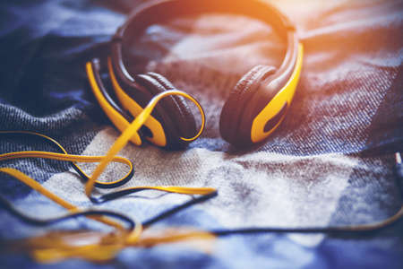 Fashionable yellow large headphones with a microphone and a long tangled wire lie on a soft plaid blanket on the bed and are illuminated by sunlight. Inspiration