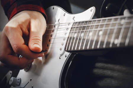 The process of playing a black-and-white electric guitar with a pick in the hand of a musician. Rock music. Skill