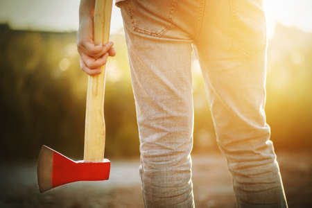 A woodcutter in jeans stands and holds in his hand his tool-an ax with a long handle and a red blade, illuminated by sunlight on a warm summer day.