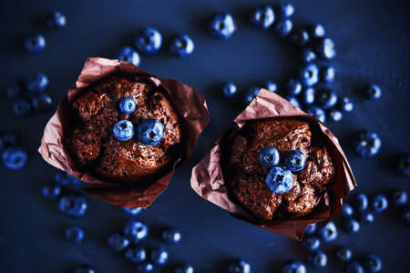 On a dark background are homemade sweet chocolate cupcakes with ripe blueberries. Homemade cake. Rich harvest of berries. Zdjęcie Seryjne