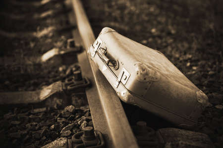 Next to the railway is an old worn-out retro suitcase, forgotten during the trip. 20th century. Immigration. Sepia. 免版税图像