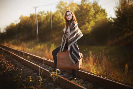 A beautiful young woman in a striped shawl travels with a retro suitcase in her hands and crosses the railway, illuminated by the rays of sunlight. Lifestyle.