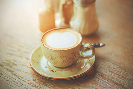 On a wooden table on a ceramic saucer is an elegant Cup of hot soft cappuccino, illuminated by sunlight. Refreshing coffee in the early morning.