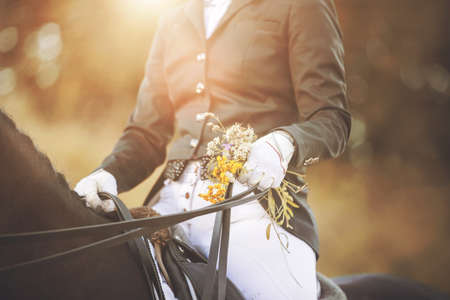 A rider sitting in the saddle on a black horse is holding a bridle rein and a bouquet of summer field herbs in the sunlight. A cute gift at an equestrian competition. Horseback riding.