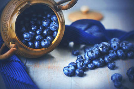 An old golden Greek bowl fell on its side on the table and spilled out the ripe blue berries of delicious blueberries. Still-life. 版權商用圖片