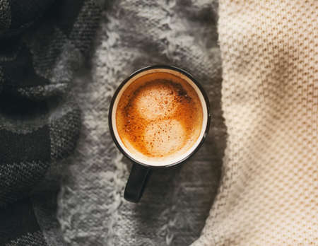 Top view of a black mug of hot, aromatic cinnamon coffee sitting on top of warm wool sweaters, prepared for the cold. The comfort of home. Hygge.