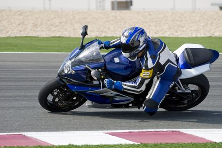 Superbike rider leaning into a corner at high speed, racing on a race track.