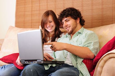Young couple relaxing on a couch, playing with a laptop computer, laughing and pointing.