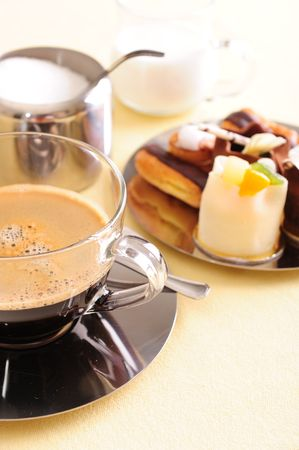 Freshly brewed coffee with a selection of pastries and cakes.r photo