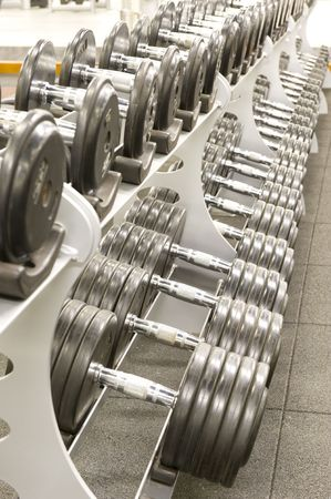 Gym or gymnasium equipment in a world-class facility suitable for athletes training for international events. Picture shows a row of dumbbells neatly stacked on their stands. Stock Photo