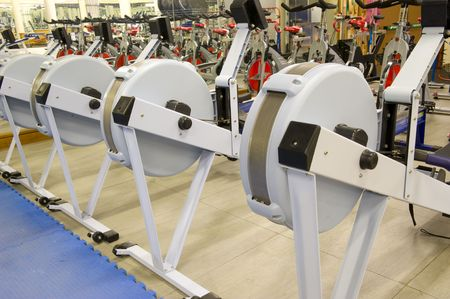 adjustable dumbbell: Gym or gymnasium equipment in a world-class facility suitable for athletes training for international events. Picture shows rowing machines.