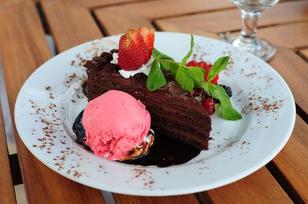 Delicious chocolate cake with various berries and a mint leaf as garnish on a brown wooden table at an outside restaurant. photo