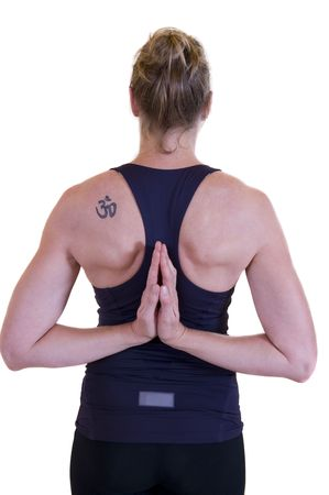 moksha: Beautiful mature lady doing yoga, hand together behind her back and showing a tattoo on the left shoulder. Stock Photo