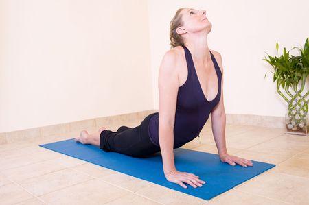 moksha: A beautiful mature lady in the Upward facing dog - Urdhva mukha yoga position, wearing a black outfit on a blue mat.
