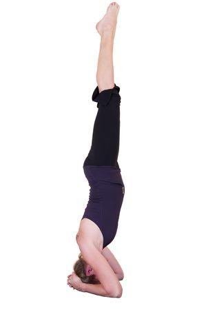 moksha: Attractive mature lady doing yoga Headstand - Salamba Sirsasana isolated on white.