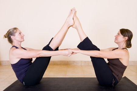 moksha: Two beautiful adult ladies in the yoga Boat pose - Navasana, facing each other and holding hands. Stock Photo