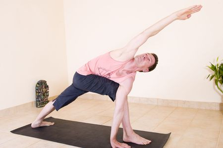 revolved: Attractive mature man in the yoga Extended side angle pose - Utthita parsvakonasana.