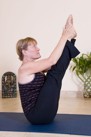 moksha: Attractive mature lady doing yoga. Stock Photo