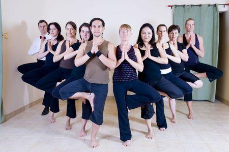 moksha: Yoga class all doing the tree pose in a V-shaped group.