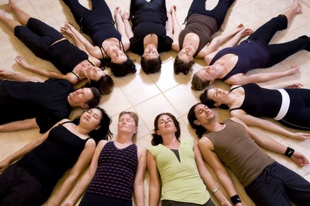 Yoga class relaxing in the Corpse pose - savasana. The group is lying in a circle with heads to the inside.