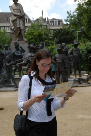 A female tourist studying a map of Amsterdam in Rembrandt square. photo