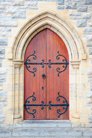 arcos de piedra: Anticuarios iglesia puerta de acero negro con decoraci�n en el arco fuera de un muro de piedra de un hist�rico edificio de la iglesia.