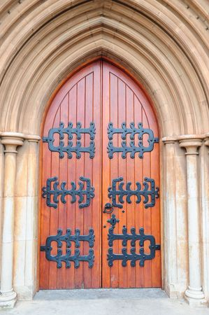 Antique church door with black steel decoration in arch on an outside stone wall of a historical church building. Stock Photo - 3408998
