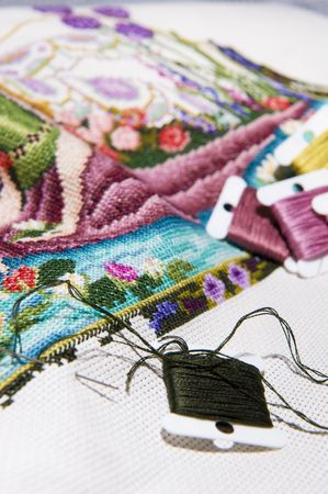 Colorful cross stitch art in the making, showing various color threads.