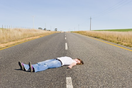 A deserted country road running through some green fields with a girl lying in the middle of the road playing dead.