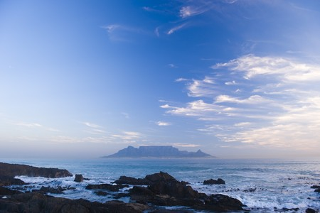 Table Mountain - the world famous landmark in Cape Town, South Africa. Picture taken on a clear Winters day from the Blouberg Strand beach. A vivid blue sky looks spectacular behind clouds in the sunset.