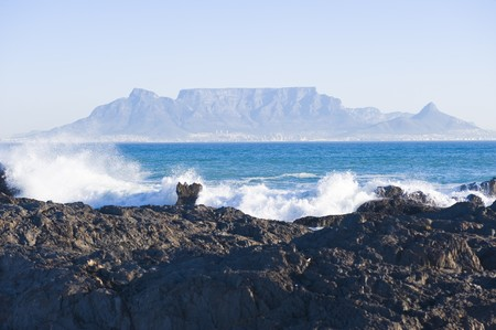 Table Mountain - the world famous landmark in Cape Town, South Africa. Picture taken on a clear Winters day from the Blouberg Strand beach. A rocky part of the beach is in the foreground.