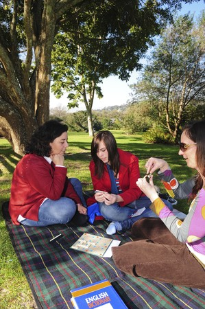 A group of ladies sitting under a tree in a beautiful lush garden, playing scrabble. photo