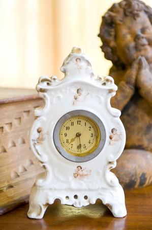 reference book: Un reloj antiguo en una mesa de madera delante de un libro de referencia de edad y la estatuilla de bronce de un �ngel.
